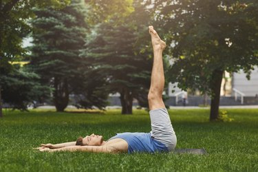 Man lying down doing lower abs exercise outdoors