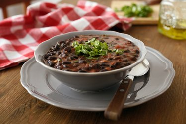 Black bean soup in a gray bowl with fresh chopped parsley on top on a gray plate on wooden table.