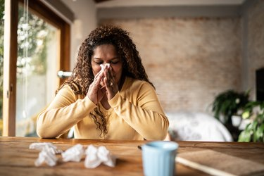 A woman sick with the flu, blowing her nose