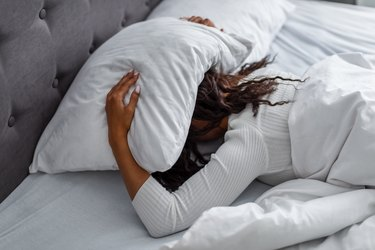 Stressed woman covering head under pillow lying in bed with hangover