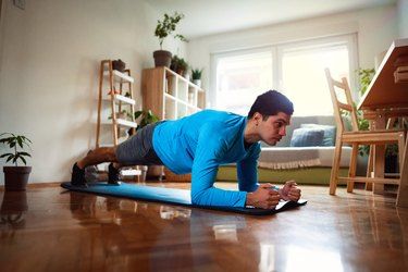 Home workout, young man doing plank in his apartment