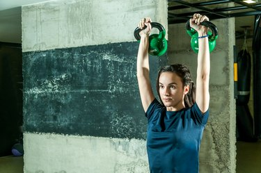 young caucasian woman doing a kettlebell shoulder press as one of the best shoulder exercises