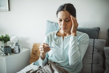 woman at home with a fever, as a side effect of the COVID vaccine