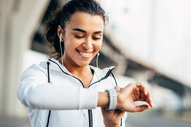 Smiling woman checking her physical activity on smartwatch. Young female athlete looking on activity tracker during training