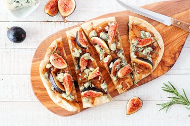 Autumn flat bread pizza with figs, caramelized onions, blue cheese and rosemary, top view table scene on white wood
