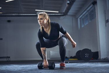 Woman doing a kettlebell exercise with a dumbbell