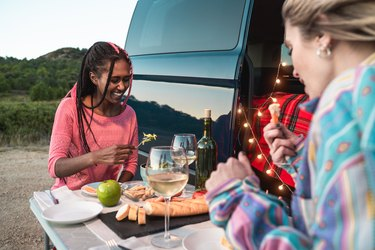 Multiracial happy friends celebrating and eating vegan food in front of camper van in park - Focus on black girl