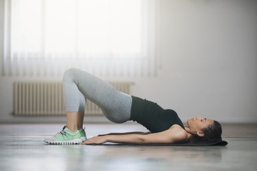 young woman doing a glute bridge workout at home