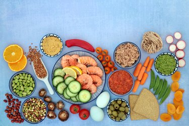Healthy fruits, vegetables, and grains in bowls against a blue background