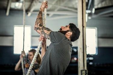Man using climbing rope at cross training gym