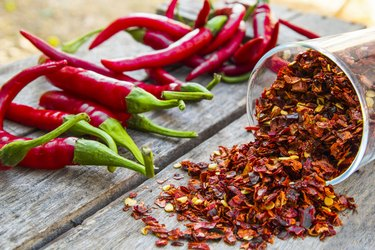 capsaicin-rich Red Pepper Flakes and red Chili on wooden table