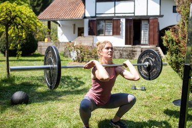 A young woman doing a front squat in her back yard