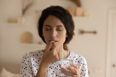 Young woman have pill with glass of water