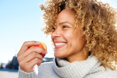 Side portrait of a woman holding an apple, one of the fruits that are good for your teeth