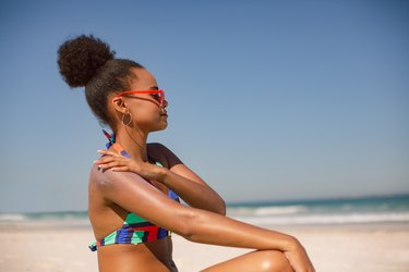Woman in bikini applying sunscreen lotion on shoulder at beach in the sunshine