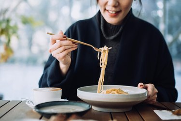 woman sitting at wooden table eating noodles with gluten from white bowl