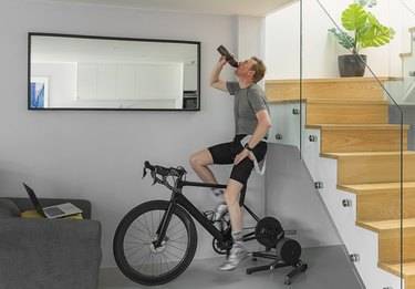 caucasian man drinking from water bottle while working out on a stationary bike at home