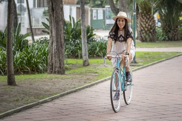 young Hispanic woman riding a bicycle in a park as an exercise to reduce inflammation