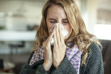 mid adult woman using a tissue for her constant runny nose