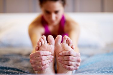Woman in pink tank top doing stretches for foot pain in bed