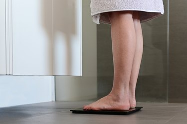 Woman measuring herself on a scale put weight