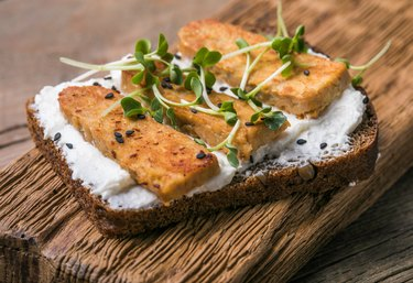 High-protein tempeh on bread with cheese and micro greens on wooden table