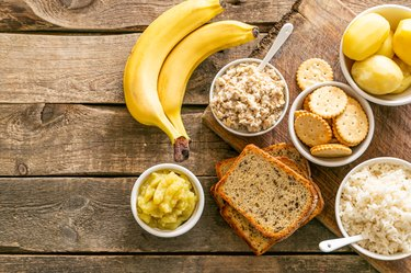 Bananas, toast, rice and crackers displayed on a wooden background