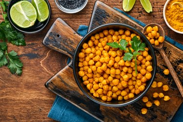 Fried chickpeas with turmeric in ceramic plate on an old wooden table background. Top view.
