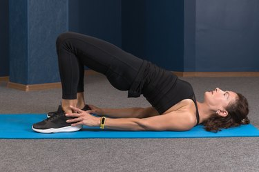 side view of mature woman in black sportswear doing a glute bridge as one of the best dynamic hip stretches on a blue yoga mat