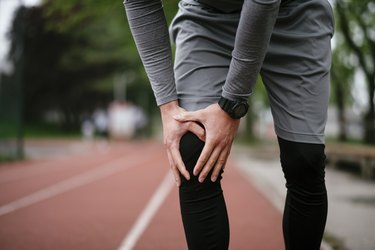 Man has pain in the knee after run outdoors.