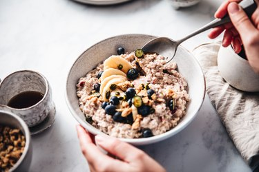 Woman making healthy breakfast with high fiber foods, as a way to treat a weak pelvic floor