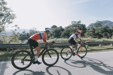 Two cyclists wearing helmets biking on the side of a road