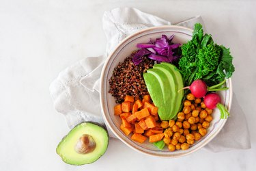 Healthy Buddha bowl with rapini, quinoa, sweet potato, chickpeas and avocado, above view over white marble