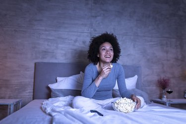 Woman smiling watching TV in bed with bowl of popcorn