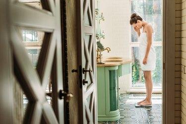 beautiful upset woman in towel standing on digital scales in bathroom