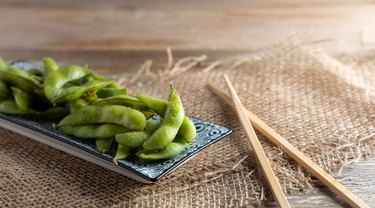 Steamed and cooked frozen green edamame soybeans on a plate.
