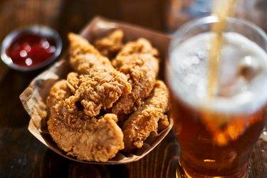 focus on fried chicken tenders in basket with beer