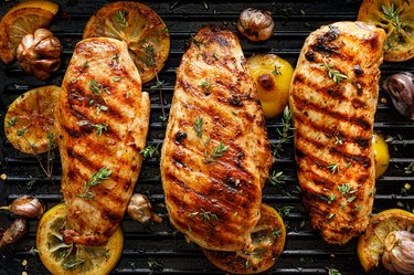 Tryptophan-rich grilled chicken breasts with thyme, garlic and lemon slices on a grill pan