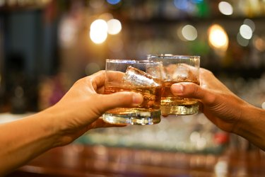 two men clinking glasses of whiskey drink alcohol beverage together at counter in the pub