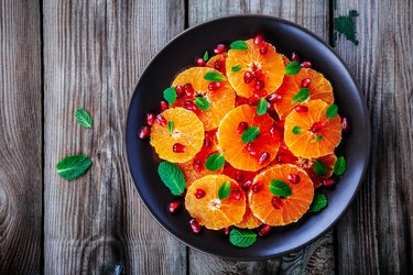 Raw fresh Citrus Salad with Oranges, pomegranate and mint on wooden background