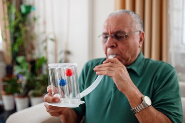 senior man with COPD measuring his lung capacity at home