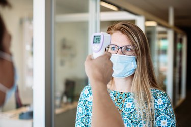Woman Has Temperature Taken By Office Worker Wearing Mask