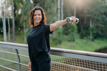 Active energized sportswoman stretches arms with dumbbell, poses on bridge over nature background with sunrise in morning, dressed in active wear, looks into distance, works on training biceps