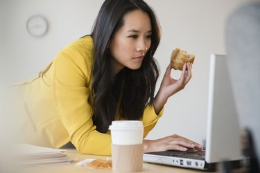 Woman eating breakfast while working on her laptop