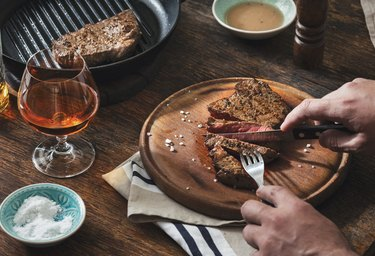 Man is eating grilled steak at wooden table