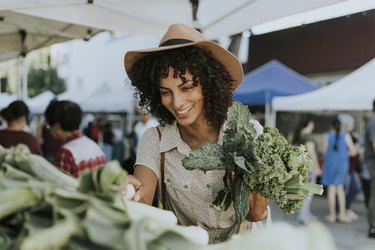 A woman at a farmers' market holds a bunch of kale