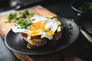 Breakfast toast with avocado, fried egg and sprouts