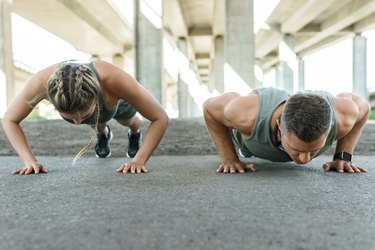 closeup of a caucasian man and woman doing burpees outside on concrete