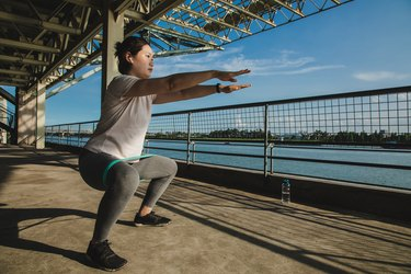 Woman doing iso squat holds with a resistance band on a pier