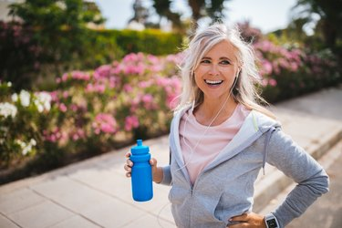 Mature woman with smartwatch holding water bottle during exercising outdoors to counter age-related memory loss